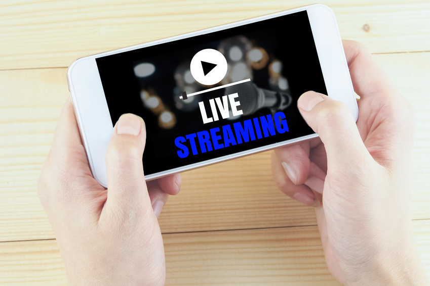 word live streaming on smartphone in hand on wooden desk